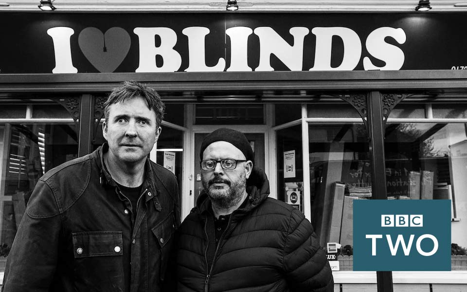 Jamie MacDonald and Jamie O'Leary standing outside a shop under the shop sign 'I Love Blinds'.