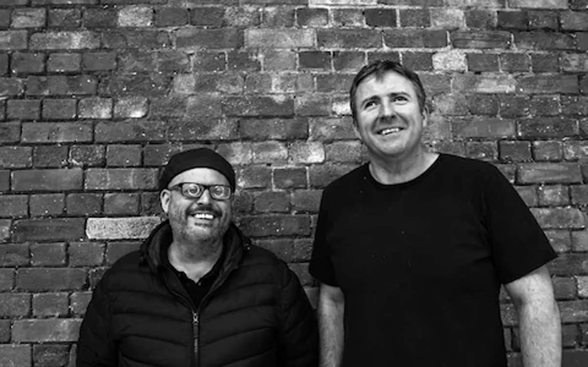 Jamie O'Leary and Jamie MacDonald smiling at camera, standing against a brick wall